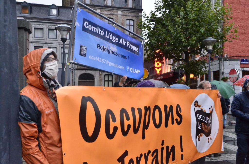 Une pancarte d'occupons le terrain et du CLAP lors d'un rassemblement à Liège