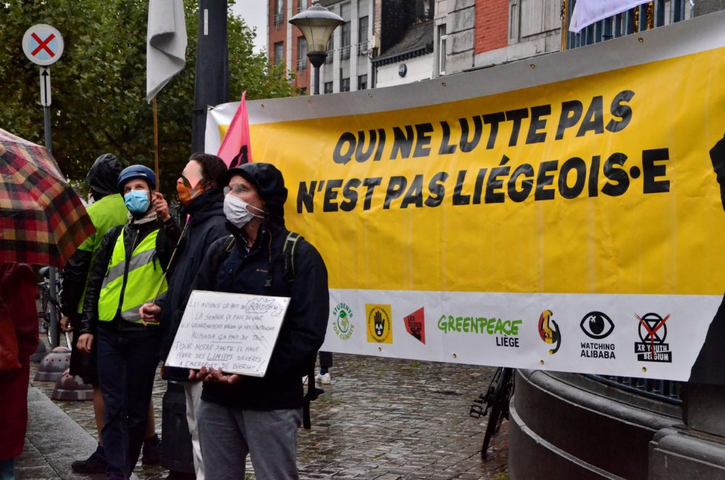 Une banderole Qui ne lutte pas n'est pas Liégeois, un homme avec une pancarte lors d'un rassemblement