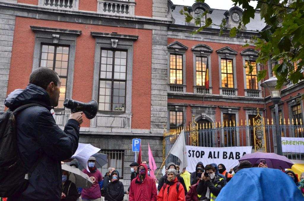 Un homme avec un parlophone devant une foule rassemblée devant l'hotel de ville de Liège